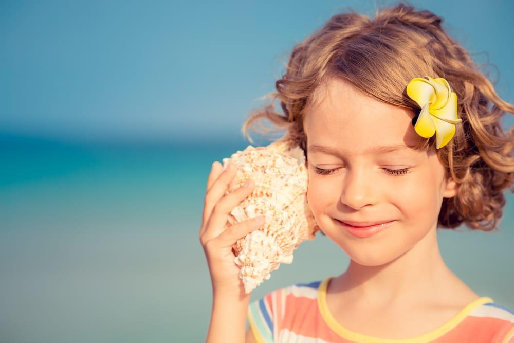niña escuchando concha